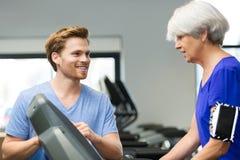 Femme âgée s'exerçant avec l'instructeur de forme physique dans le gymnase Images libres de droits