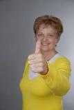 Femme âgée souriant avec le pouce vers le haut Photo stock