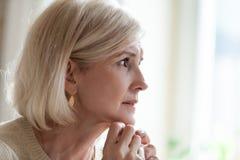 Femme âgée triste pleurant près du sentiment de fenêtre isolé photos stock