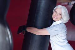 Femme âgée vivace étreignant le punchbag Photo stock