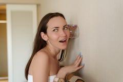 Femme écoutant clandestinement par le mur de la salle par une tasse en verre, curiosité, espionnage, visage étonné, émotions vive photo stock
