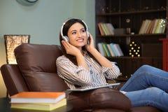 Femme écoutant l'audiobook par des écouteurs Photo stock