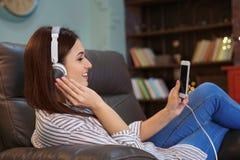 Femme écoutant l'audiobook par des écouteurs Photos stock