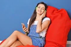 Femme écoutant l'audiobook par des écouteurs Photographie stock libre de droits