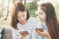 Femme écoutant la musique en parc du téléphone Et amis vivant ensemble, un mode de vie dans leurs vacances Image stock