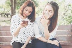 Femme écoutant la musique en parc du téléphone Et amis vivant ensemble, un mode de vie dans leurs vacances Images stock