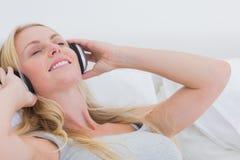 Femme écoutant la musique tandis qu'elle est étendue dans son lit Image libre de droits