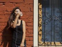 Femme écoutant le café msuic et potable Photographie stock