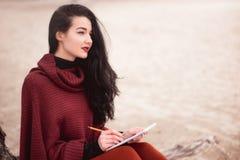 Femme écrivant dehors Photographie stock libre de droits