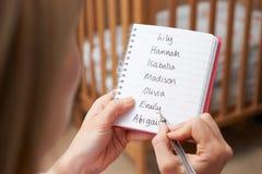 Femme écrivant des noms possibles pour le bébé dans la crèche images libres de droits