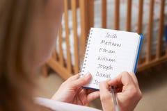 Femme écrivant des noms possibles pour le bébé garçon dans la crèche images stock