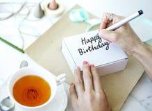 Femme écrivant le joyeux anniversaire sur un boîtier blanc Images stock