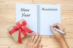 Femme écrivant le mot de 2019 résolutions de nouvelle année avec le carnet et la décoration de Noël sur la table en bois, la vue  photo libre de droits