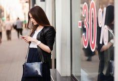 Femme élégante à l'aide d'un téléphone portable devant des boutiques d'étalage, remise de 30 pour cent Photographie stock