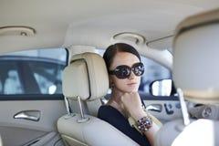 Femme élégante avec de longues pattes dans le véhicule Image stock