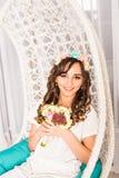 Femme élégante avec des fleurs dans un intérieur blanc photo libre de droits