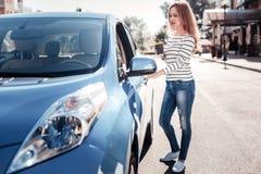 Femme élégante calme se tenant près de la voiture tenant le café Photographie stock