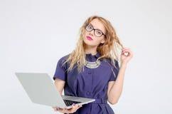 Femme élégante d'affaires dans un costume avec des verres et un ordinateur portable Photographie stock libre de droits