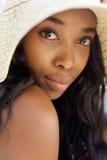Femme élégante d'afro-américain avec le long chapeau de cheveux et de soleil photographie stock