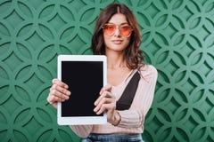 Femme élégante dans des lunettes de soleil oranges montrant la tablette et le regard photo libre de droits