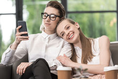Femme élégante dans des lunettes utilisant le smartphone avec l'amie de sourire tout près Photos libres de droits