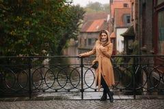 Femme élégante dans la position brune de manteau sur le pont dans Bealgium, Bruges La femelle a mis dessus un capot photos stock