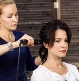 Femme élégante dans la salle de beauté Le coiffeur fait la coiffure sous forme de grande boucle Coiffure de mariage de concept images stock