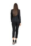 Femme élégante dans le costume de noir d'affaires marchant loin blanc d'isolement de vue arrière Image libre de droits