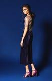 Femme élégante dans le pantalon bleu de plissé et des chaussures violettes Photos libres de droits