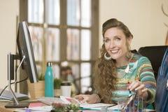 Femme élégante dans un bureau créatif encombré image stock