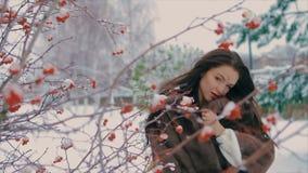 Femme élégante de brune près de buisson avec le mouvement lent de baies rouges banque de vidéos