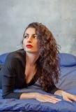 Femme élégante de brune se situant dans le lit Photographie stock libre de droits