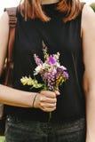 Femme élégante de hippie avec le sac à dos recueillant et tenant le wildf Photographie stock