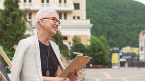 Femme élégante de sourire ayant un repos sur la rue avec la beaux nature et bâtiments clips vidéos