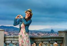 Femme élégante de sourire de voyageur montrant les mains en forme de coeur Images stock