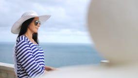 Femme élégante de vue de côté dans le chapeau et des lunettes de soleil admirant la mer et ciel au balcon ou à la terrasse banque de vidéos
