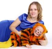 Femme élégante et la fille dans un procès d'un tigre Image stock