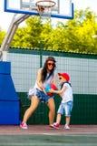 Femme élégante et petit garçon jouant le basket-ball Photo stock