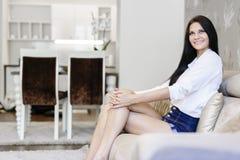 Femme élégante et sexy s'asseyant sur un sofa dans une salle luxueuse photo libre de droits