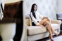 Femme élégante et sexy s'asseyant sur un sofa dans une salle luxueuse photographie stock libre de droits