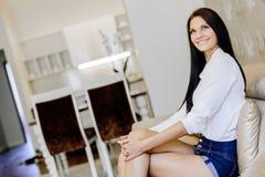 Femme élégante et sexy s'asseyant sur un sofa dans une salle luxueuse images stock