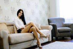Femme élégante et sexy s'asseyant sur un sofa dans une salle luxueuse image stock