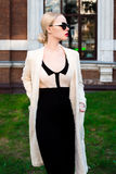 Femme élégante européenne blonde de mode heureuse avec les lèvres rouges et la peau blanche se tenant au vieil immeuble de brique Image libre de droits