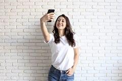 Femme élégante faisant le selfie avec le panier sur le fond jaune de mur Vente de vacances d'hiver Photographie stock