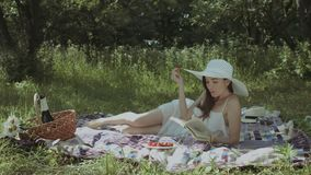 Femme élégante lisant un livre en parc d'été banque de vidéos