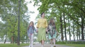 Femme élégante mûre marchant en parc avec ses deux petite-filles Mains heureuses de fixation de famille Dépense de grand-mère banque de vidéos