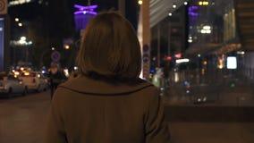 Femme élégante marchant la vue arrière, appréciant égalisant la promenade dans la ville lumineuse banque de vidéos