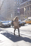 Femme élégante parlant à son téléphone traversant la rue à New York Photos libres de droits