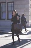 Femme élégante parlant à son téléphone traversant la rue à New York Images libres de droits