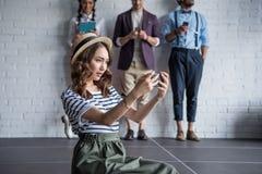 Femme élégante prenant le selfie sur le smartphone tandis que ses amis à l'aide des dispositifs numériques Photos stock